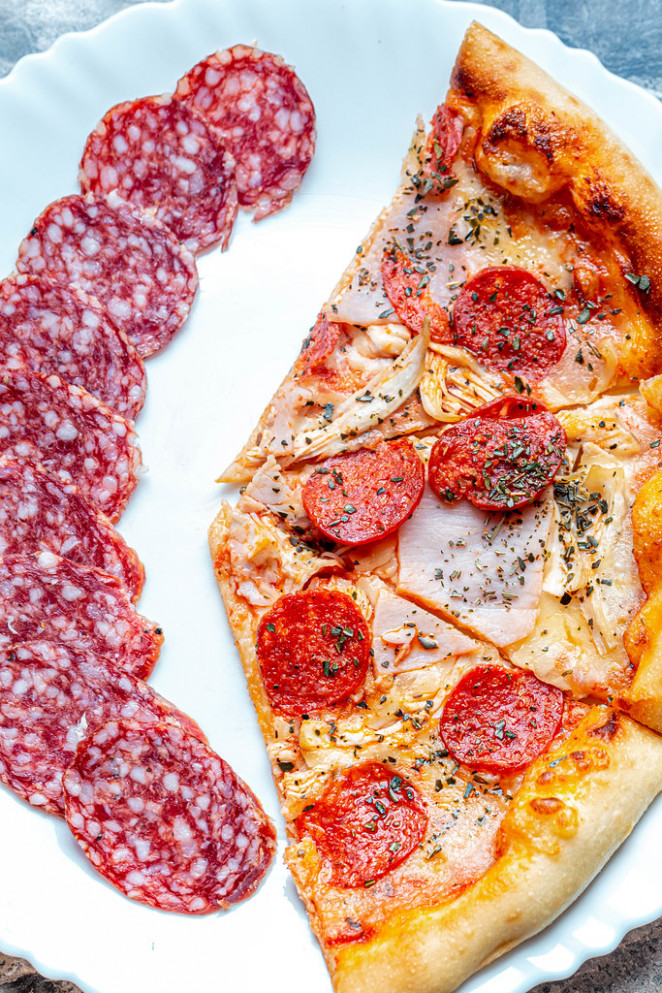 Slices of meat pizza with sliced smoked sausage on a white plate (Flip 2019) (Flip 2019)