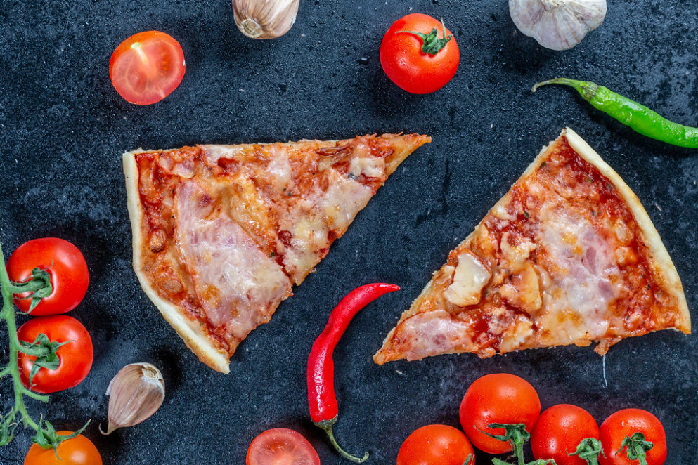Two slices of homemade pizza on a black background with vegetables